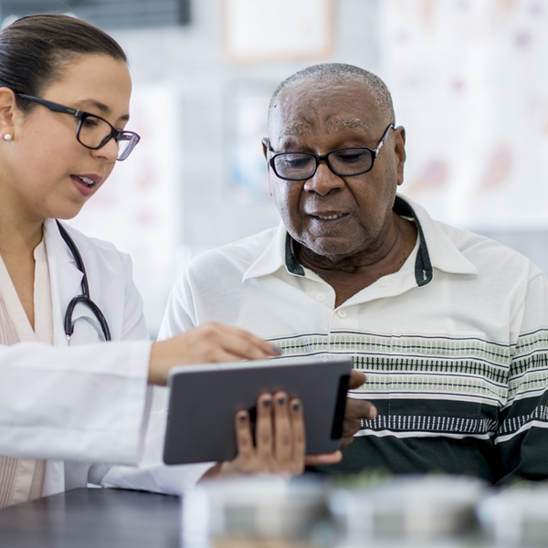 Doctor talks with patient while looking at a tablet