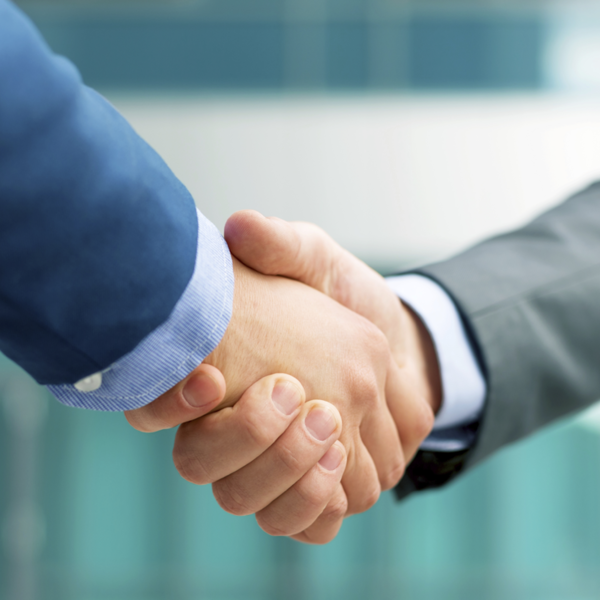 Two men wearing suits shaking hands