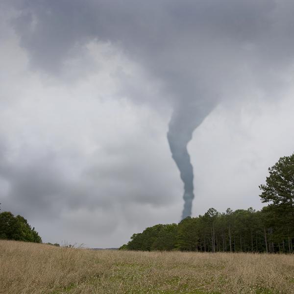 A tornado whirls over a field.