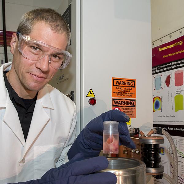 Man in lab coat holding scientific equipment