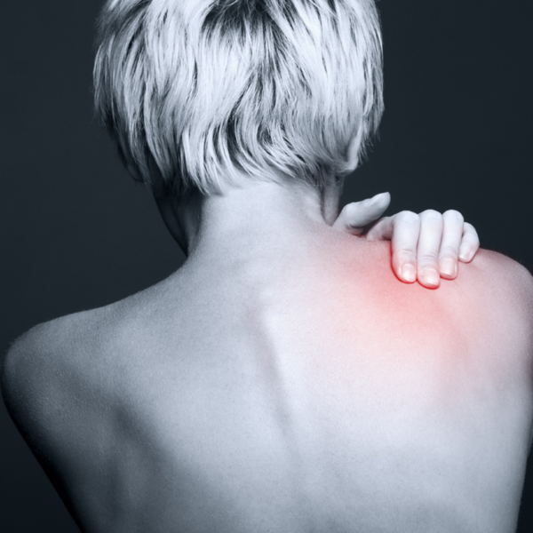 Black and white photo of a women holding her back where she has pain