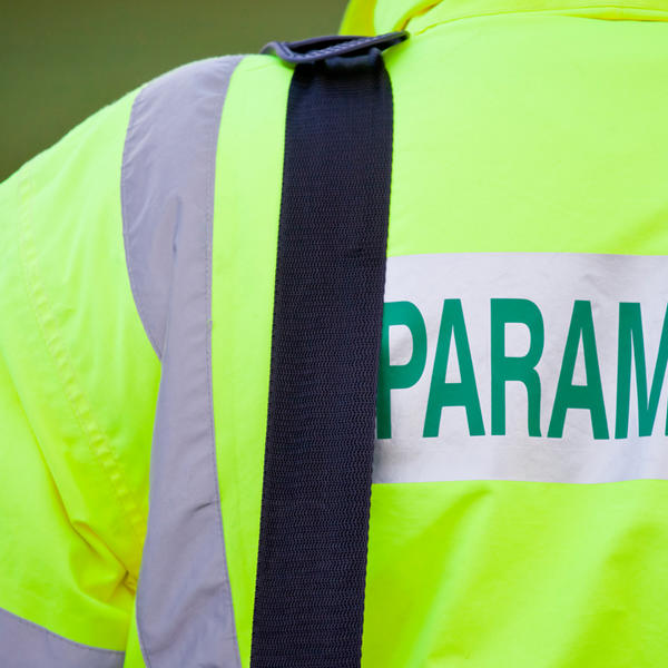 """A person wearing a yellow jacket with the word """"paramedic"""" across the back"""