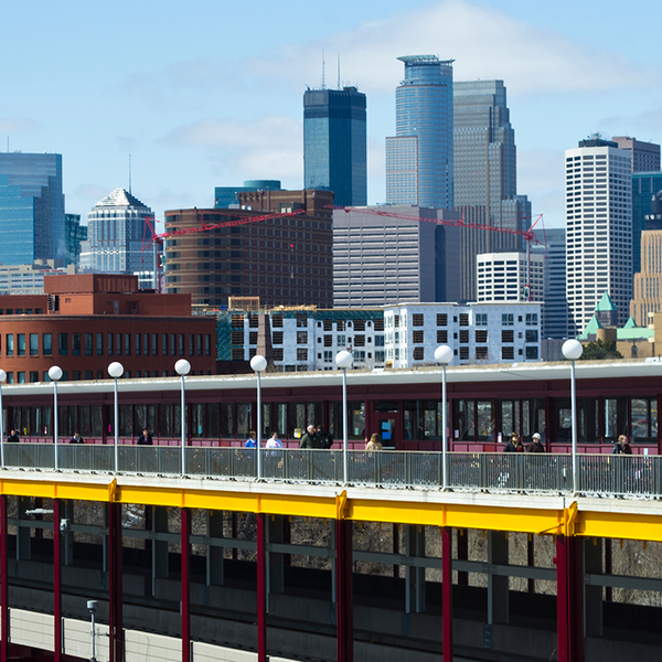 Photo of Washington Avenue bridge on UMN campus with Minneapolis skyline in the background.