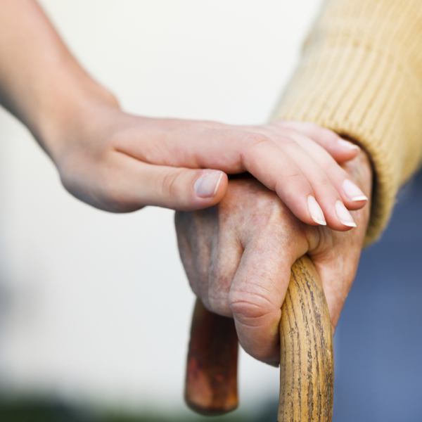 Caretaker holds the hand of a man using a cane