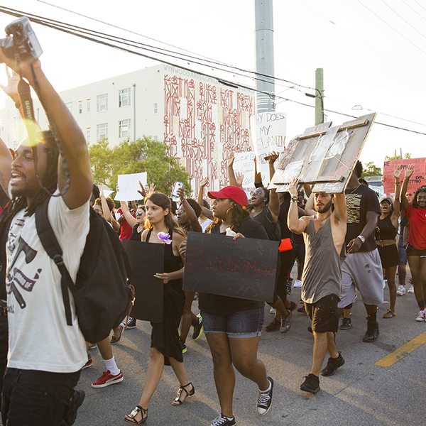 People march in protest down a street while holding signs