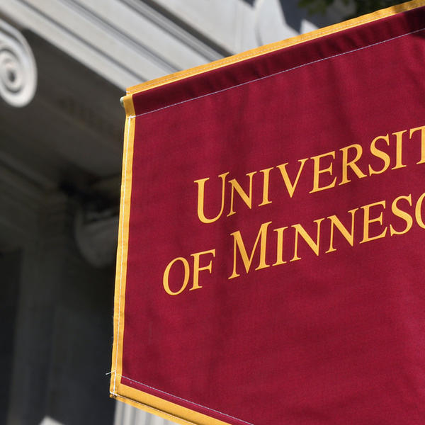 A U of M flag near a building with columns