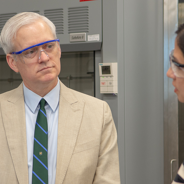 Close up shot of VP Cramer listening to a researcher speak in a laboratory