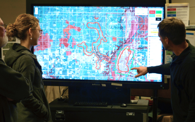 Researchers involved in a MnDRIVE project to maximize the benefits of biomass use touch screen visualization to partner with regional farmers on how to get the most out of the land.