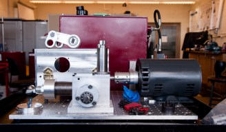 An array of components collected on the test table, including the original pump in the foreground. Behind it, a linkage assembly rests on top of the new pump. The improved model is five times more powerful than the electric motor (right) used to run tests