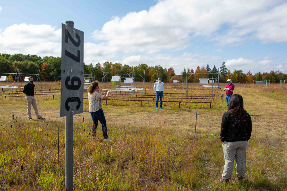 group of people stand among prairie research plots with various hardware contraptions and signs