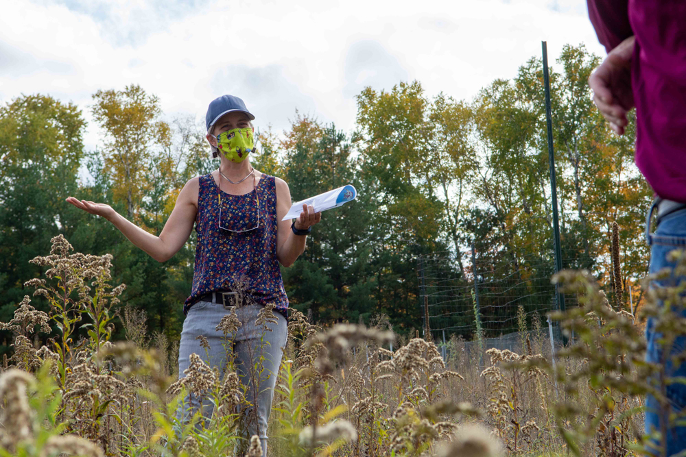 Person standing in prairie grass explaining to observers with hand gestures.