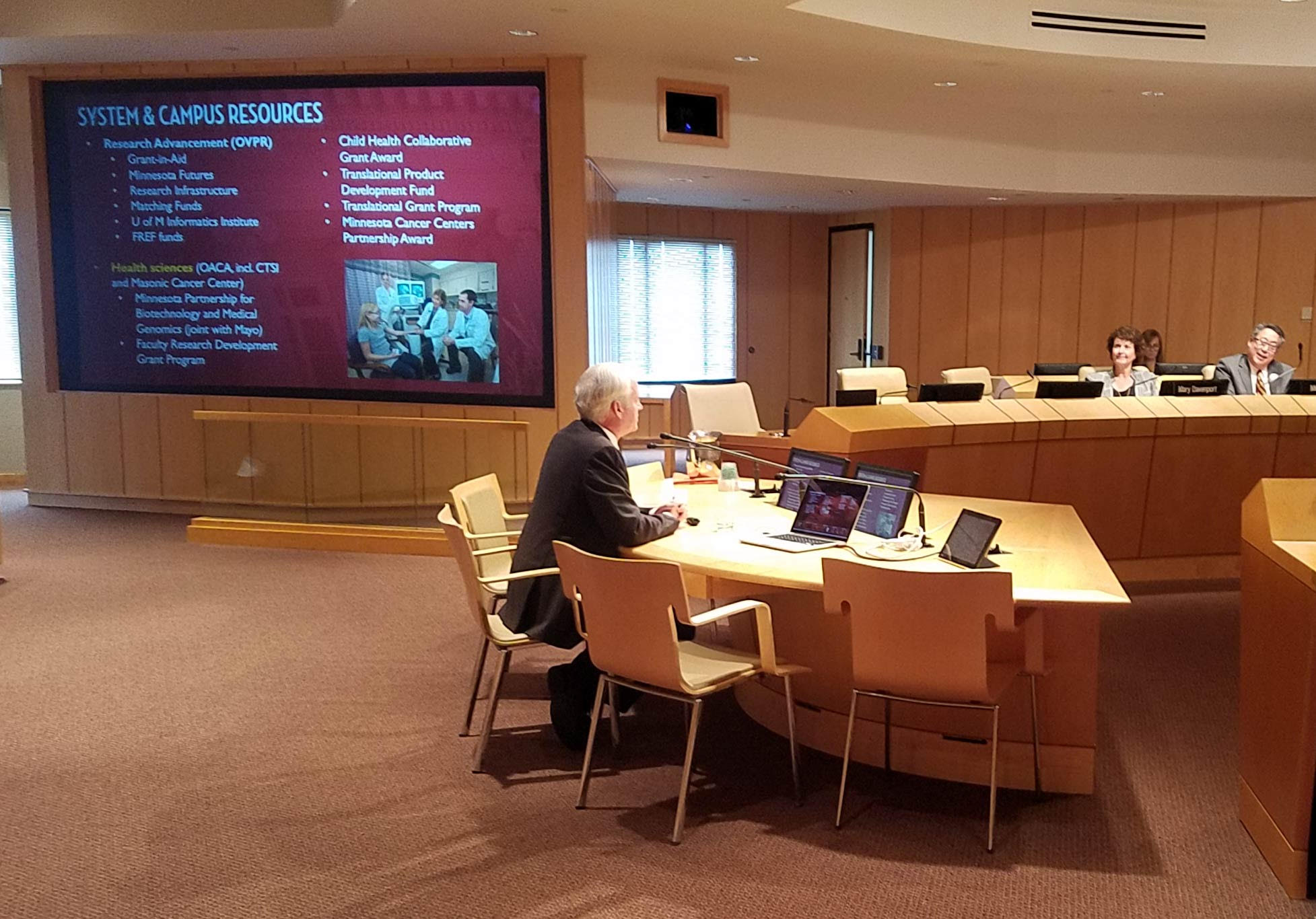 VPR Cramer sits at a table to present at the October 11 Board of Regents meeting. Slide from his presentation is projected behind him.